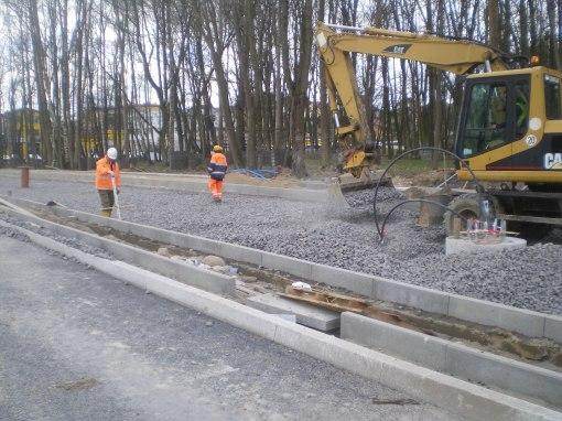 Budowa linii tramwajowej przy alei Sikorskiego (17 kwietnia 2015) - układanie podsypki (tłucznia)